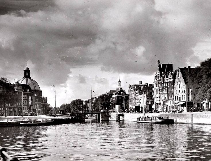 1950's. A view of Open Havenfront in Amsterdam. In the background the Haarlemmersluis and Ronde Lutherse Kerk (left). Open Havenfront is a canal between Prins Hendrikkade and Stationseiland. The canal connects with Damrak, Singel and the IJ. On the east-side is the famous Noord-Zuid Hollandsch Koffiehuis located. There are three bridges crossing the Open Havenfront, the Westelijke Toegangsbrug, Middentoegangsbrug, and Kamperbrug. Photo Stadsarchief Amsterdam. #amsterdam #1950 #OpenHavenfront