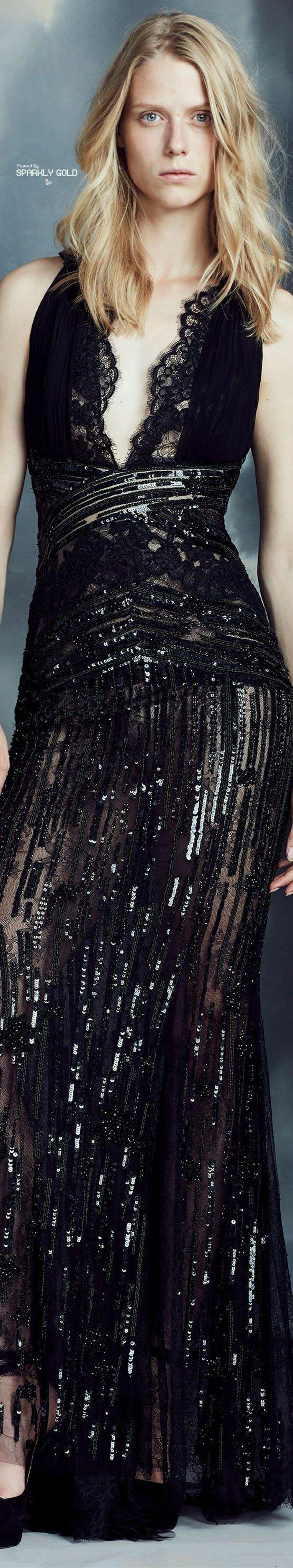 sehr langes schwarzes halbdurchsichtiges Kleid mit Spitze und Pailletten und mit einem sehr tiefen Ausschnitt, getragen von einer Blondine mit leicht gewellten Haaren und hellblauen Augen