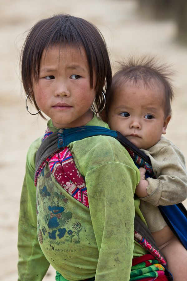 Hmong Tribe children in northern Vietnam……BIG SISTER IS HIS CARETAKER WHILE MOM AND DAD ARE WORKING IN THE RICE PADDIES………..ccp