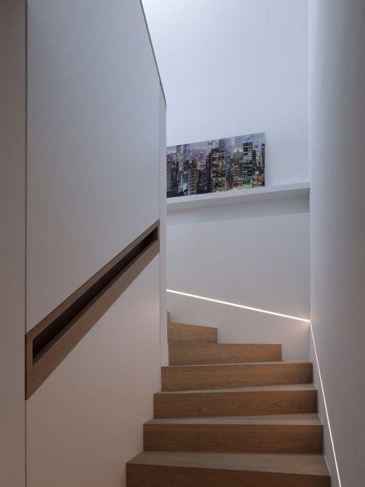 Light strip along staircase. I also like the skinny running shelves in stairway.