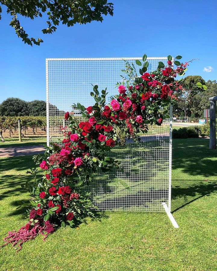 ca446c4984e2 Three Contemporary Ceremony Backdrops ~ bold red   pink blooms by Signature  Floral Design adorn a mesh screen by Maisey Collections
