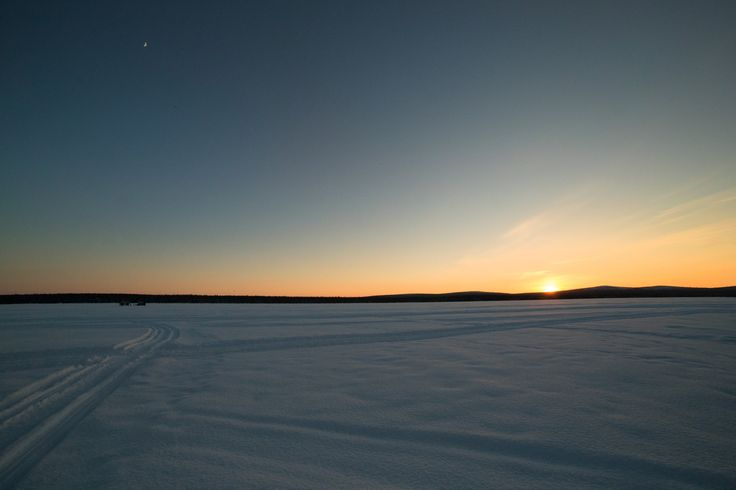 Snowmobile highways - Snowmobile highways at sunset. Sauna in the distance on the frozen lake.