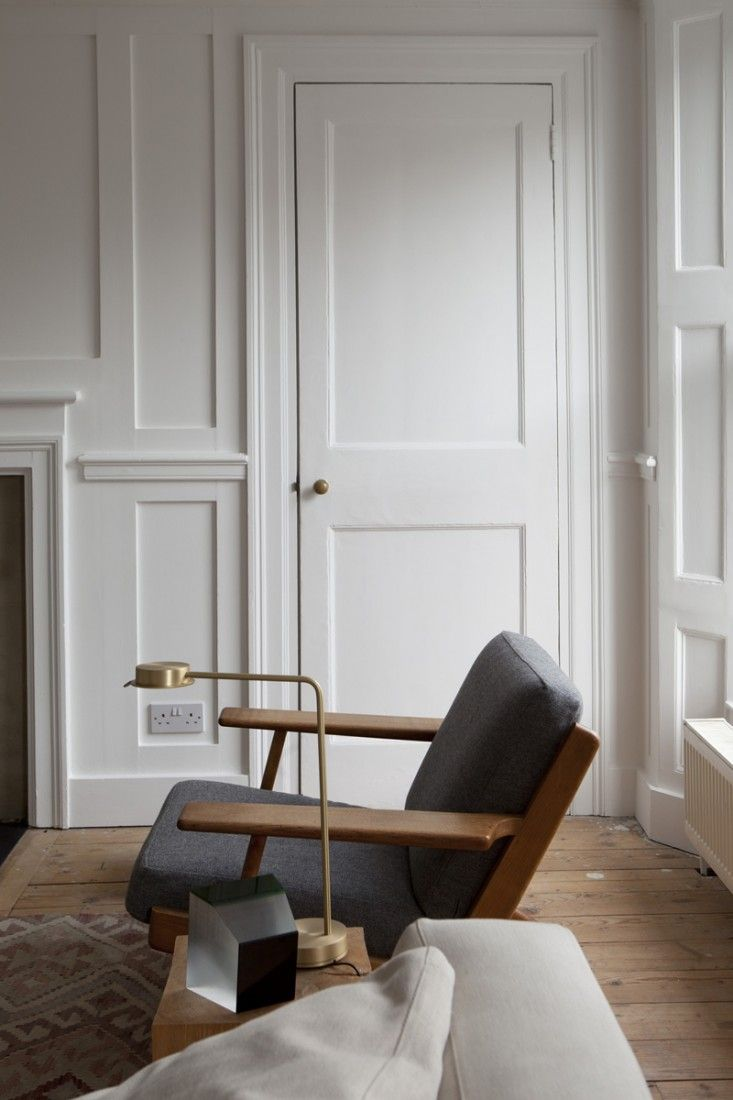 William Smalley flat in Bloomsbury, wood floors, white paneled walls, Wegner chair | Remodelista