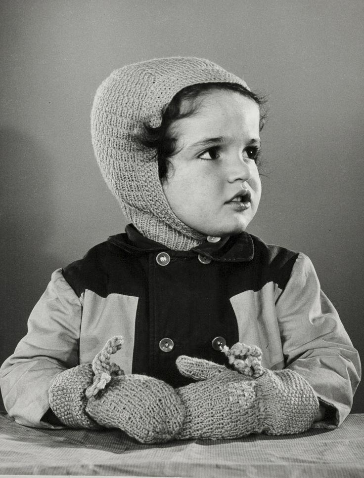 Kindermode: studio-opname van meisje (kleuter) met winterjas aan en gebreide wanten en bivakmuts. Nederland, 1950-1960.