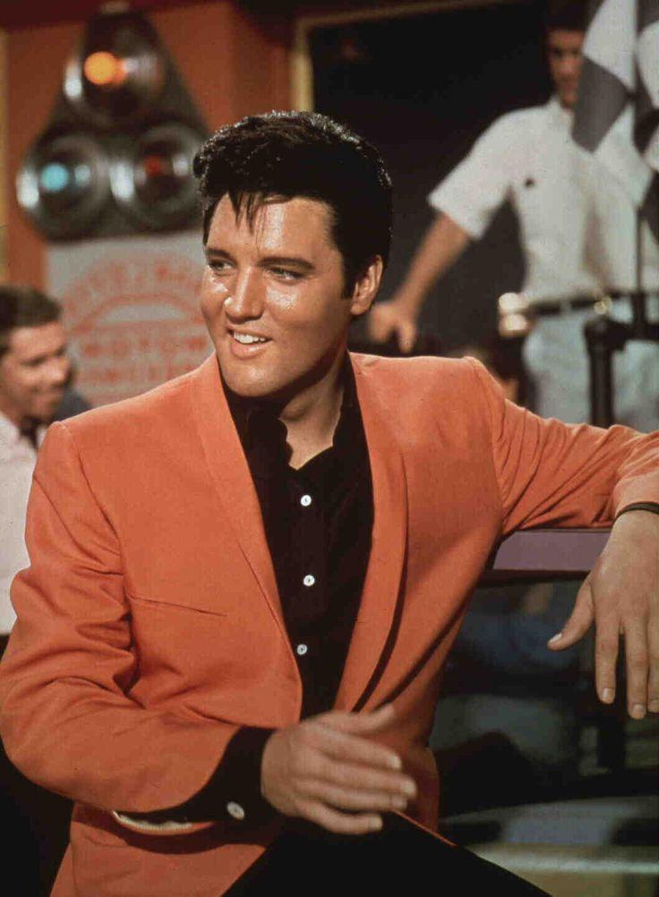 """Speedway"" Color scene still  | Elvis Presley as Steve Grayson wearing sports coatt looking off to side as two men stand in background."