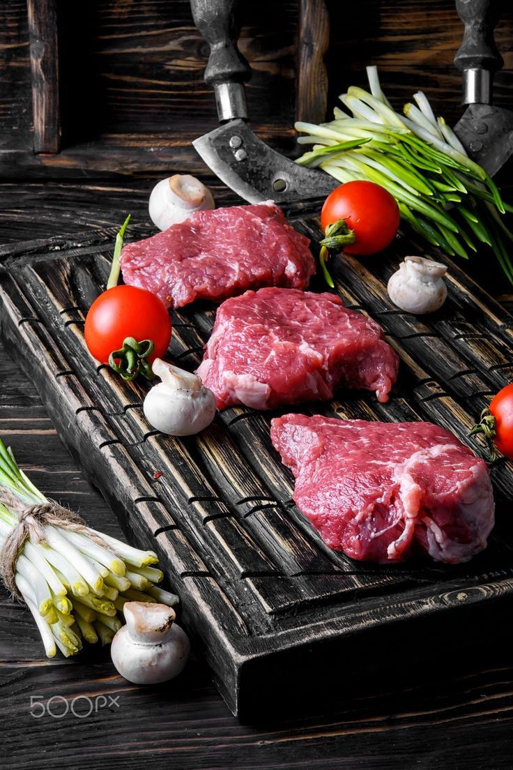 Fresh meat home beef - still life with fresh juicy veal steaks with wild garlic and tomatoes