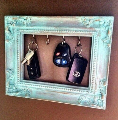 DIY keyhanger -- twist screw hooks into wooden picture frame. Use velcro strips to hang frame