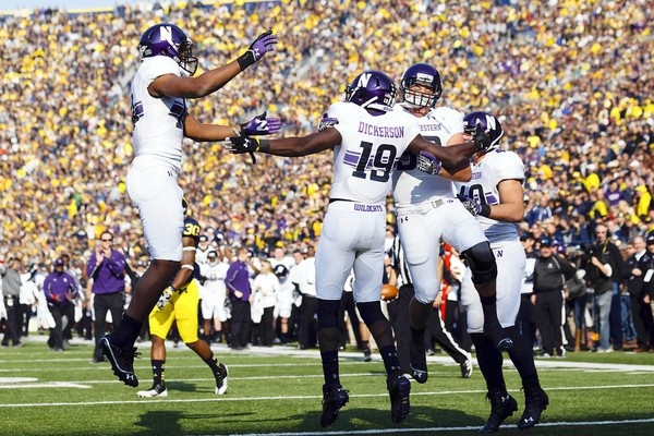 Northwestern wide receiver Cameron Dickerson receives congratulations from teammates after scoring a touchdown in the second quarter. #Northwestern #Michigan