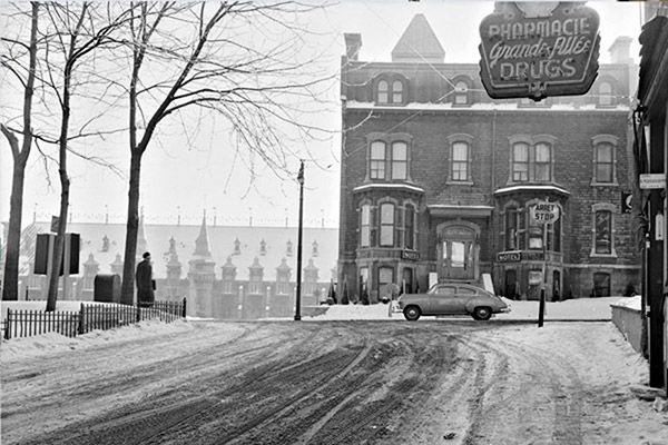En 1952, l'intersection de la rue d'Artigny et la Grande Allée n'avait pas de terrasse, alors que la rue était collée sur l'immeuble qui abritait à l'époque une pharmacie.