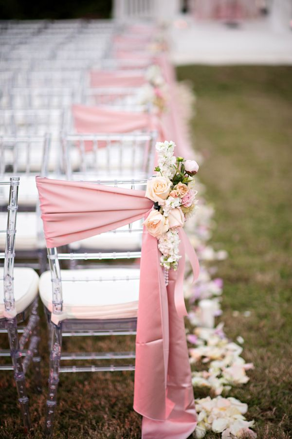 Clear Chiavari chairs with satin pale pink sashes with floral accents. Photographed by @Kristen Weaver Photography