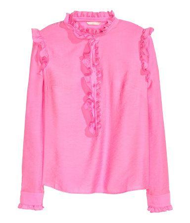 Roze. Een wijde blouse van geweven viscose met een halsboordje, een front en lange mouwen. De blouse heeft een volantrandje langs de halsopening en het