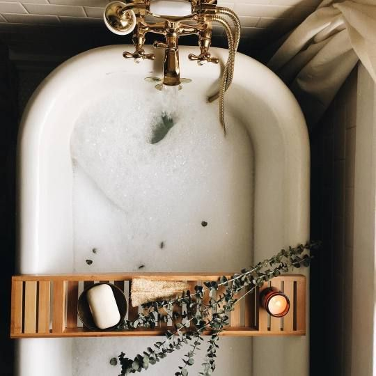claw bubble bathtub with brass fixtures and tray to hold candles, soaps, and aromatherapy