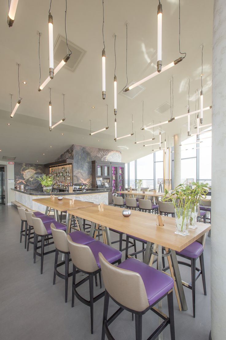 Contemporary Industrial Pendant Lighting. Lilac and Champagne bar stools with modern timber tables with metal chopstick legs. Bar Design by Tibbatts Abel. www.tibbattsabel.com