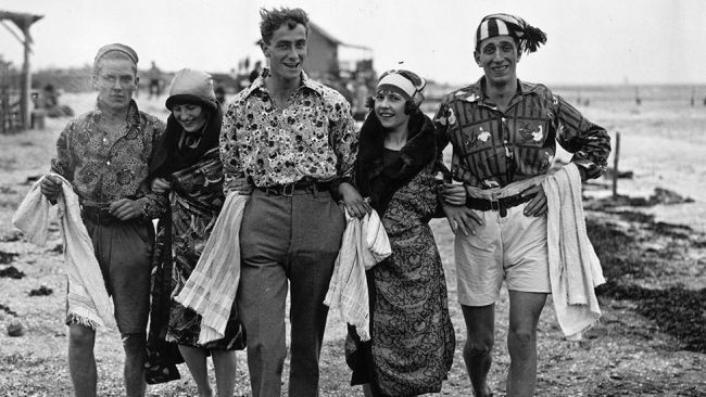August 1922: A group is seen walking on the beach at Canvey Island, Essex. (MacGregor/Topical Press Agency/Getty Images)