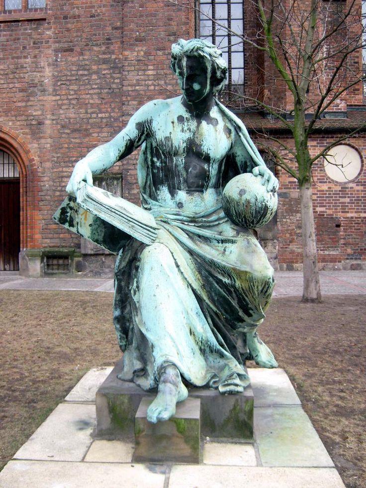 """Bronzeskulptur """"Allegorie der Wissenschaft"""" vor der Nikolaikirche an der Poststraße im Nikolaiviertel in Berlin-Mitte. Albert Wolff schuf die Skulptur zwischen 1860 und 1871 als Sockelfigur für das Denkmal des preußischen Königs Friedrich Wilhelm III. im Lustgarten"""