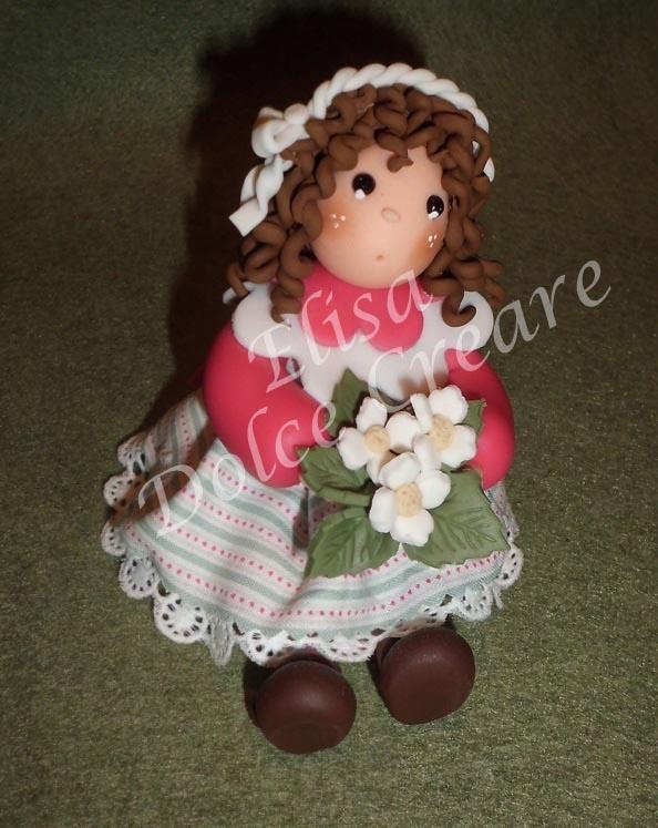 Bambolina bianca e fucsia con vestito a righe in pasta di mais