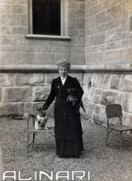 Ritratto della Regina Margherita di Savoia, vestita con abito a lutto, mentre accarezza un piccolo cane accucciato su una sedia di vimini. #TuscanyAgriturismoGiratola