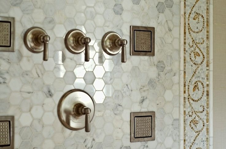 Incredible bathroom shower with carrara marble tiles, polished marble hexagonal tile with stunning mosaic, vine border.