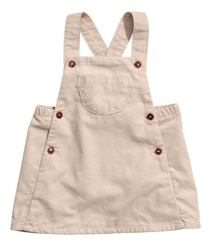 Hellbeige. BABY EXCLUSIVE. Latzrock aus Baumwollcord. Träger mit Knöpfen, eine Brusttasche, schmaler Gummizug in der Taille und Knöpfe an den Seiten.