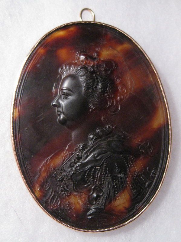 Cameo medallion of Queen Anne, circa 1705, by John Obrisset (105-1738); Belfor Antiques.  Tortoise shell with 15k rose gold.  Antiques.com (http://www.antiques.com/classified/1054659/John-Obrisset-Tortoise-Shell-Cameo-C-1705#).