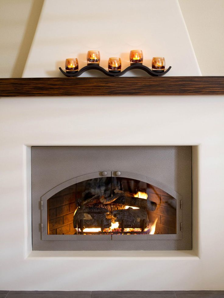 A stunning adobe fireplace is given a modern update in this Southwestern-inspired living room on HGTV.