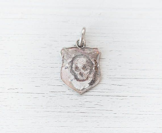 This is a vintage travellers charm made of sterling silver. The enamel was worn off the charm so I decided to experiment with it. I engraved and enhanced with patina this little skull to make it look like grafitty on an old water stained wall. It is an old and worn little bracelet charm