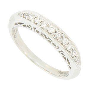 This elegant 14K white gold wedding band is brightly polished and set with a string of round faceted diamonds. The sides of the wedding ring are embellished with a bold scrolling filigree decoration. The sparkling ring measures 3.29 mm in width. Size 5 1/2. We can re-size.