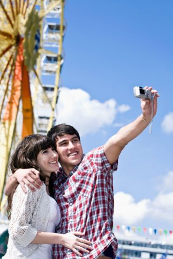 portrait teenage couple taking photo of themselves at fun fair