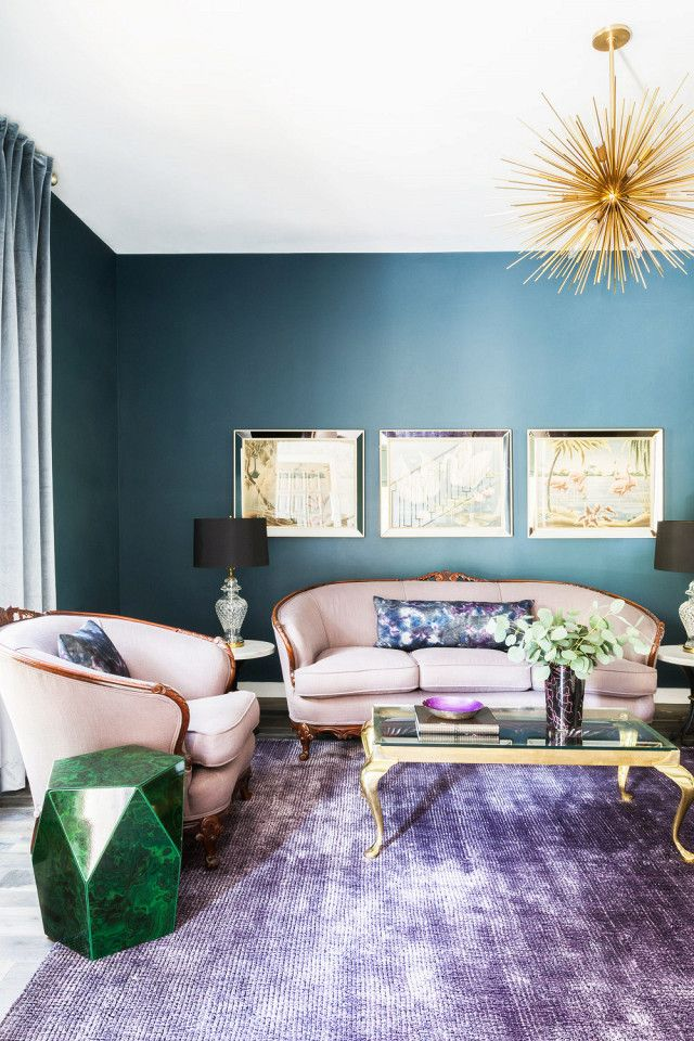 Formal living room with a vintage reupholstered  loveseat, an eggplant-colored rug, deep blue  walls, and metalic accents