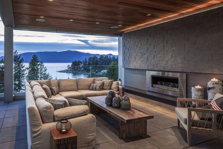 Salon aux assises confortables aménagé d'une cheminée moderne, avec belle vue sur l'eau