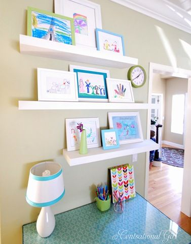 Fun way to display kid art.  I also like how she placed fabric on the desk top and hot glued ribbon to the lamp.