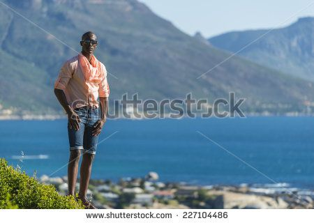 http://www.shutterstock.com/pic-227104486/stock-photo-african-black-man-standing-on-a-high-rock-overlooking-cape-town-as-he-points-and-scouts-the-blue.html?src=WuffEuvvGWj02MQSGcnIHQ-1-13 African Black Man, Standing On A High Rock Overlooking Cape Town As He Points And Scouts The Blue Sky, Ocean And Mountains On A Sunny Summers Day Stock Photo 227104486 : Shutterstock