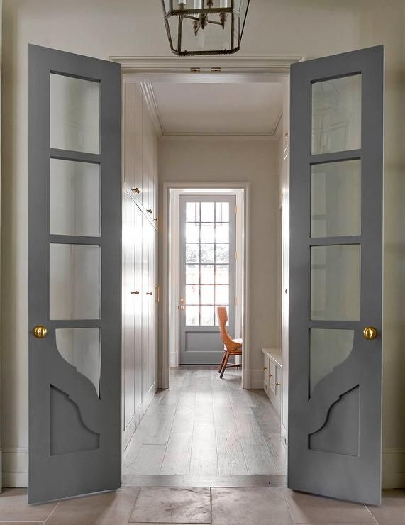 Gray bi-fold doors with glass panels open to a long and narrow mudroom filled with floor to ceiling light gray cabinets facing a light gray mudroom bench as well as a small home office filled with a built-in desk and an orange chair.