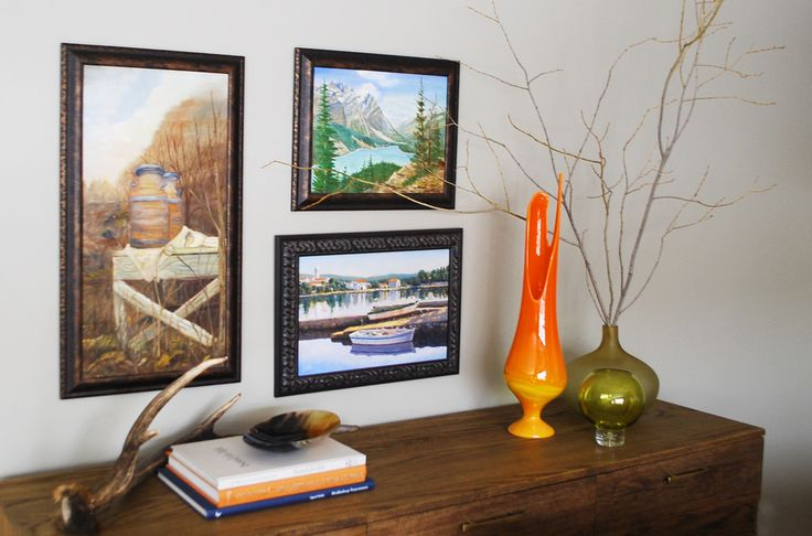 landscape paintings hung over midcentury modern console table
