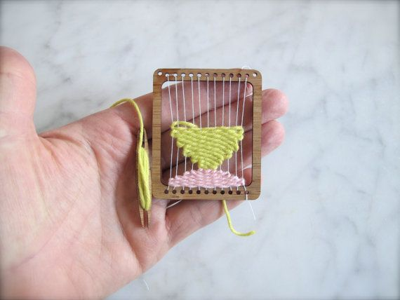 One miniature weaving loom and shuttle. This can be used to make miniature woven tapestries or you can leave your weaving in the loom and wear as