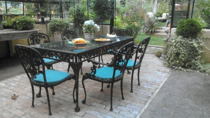 $600.00 Vintage wrought iron outdoor dining set with glass top, 6 chairs and cushions