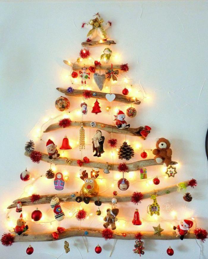 arbre de noel en bois flotté avec plusieurs jouets et boules lumineuses