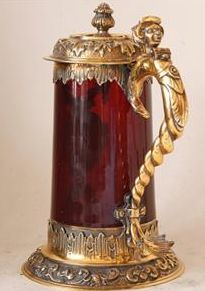 Antique ruby red glass and sterling silver beer stein made in England over 150 years ago during the beginning of Victorian era. Tapered crystal glass ruby-red body with polished-out pontil mark. Very ornate silver mounts repousse, chased and heavily gilt. Solid handle with Faun head for the thumb lift.