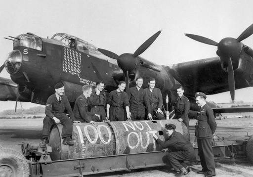 The ground crew of RAF Waddington, Lincolnshire, May 1944 'bomb up' a Lancaster of No.467 Squadron RAAF writing on a 'Cookie' (8,000 lb HC (High Capacity) bomb) '100 Not Out' to mark the 100th recorded operation of the Lancaster PO-S R5868. [AWM SUK12226]