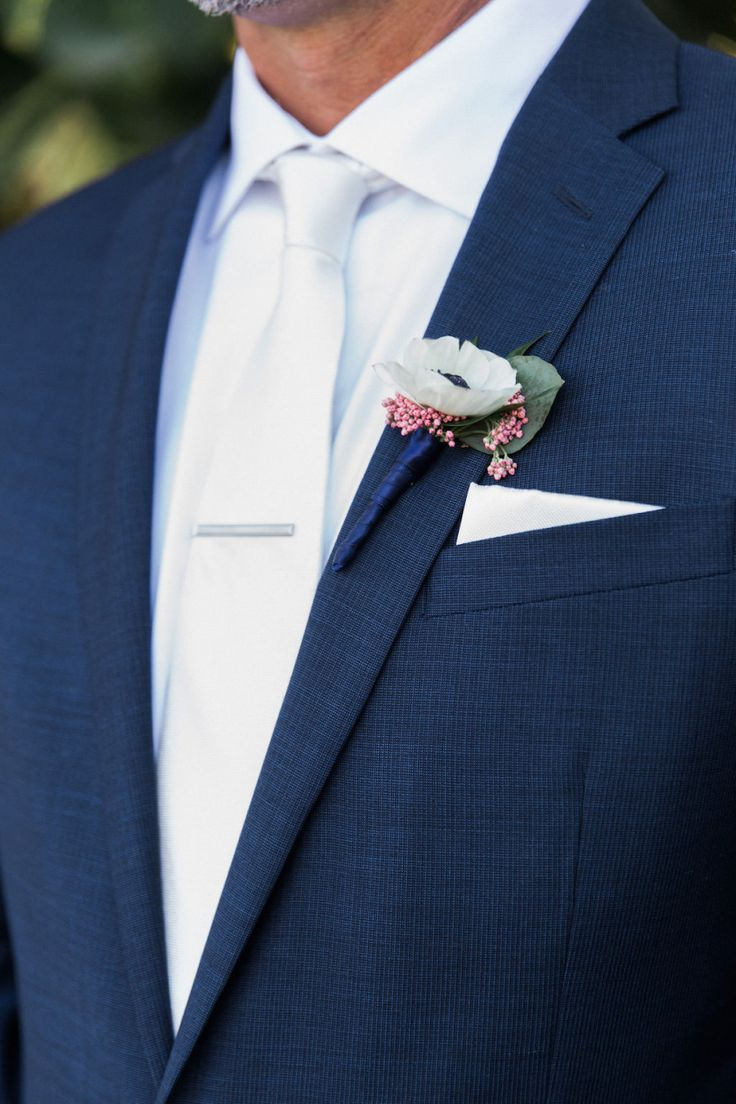 Groom with White Anemone and Pink Blossom Ribbon Wrapped Boutonniere, White Silk Tie, and Navy Suit