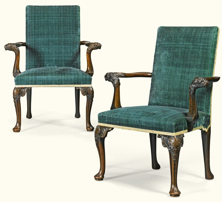 A pair of George II carved mahogany open armchairs, circa 1750 each with square padded back and seat, covered in a contemporary silk velvet, with outswept arms and carved lion mask terminals on downswept supports joined to the side of the seats, on shell carved cabriole legs flanked by acanthus, with stop fluted cabriole legs, ending on pad feet