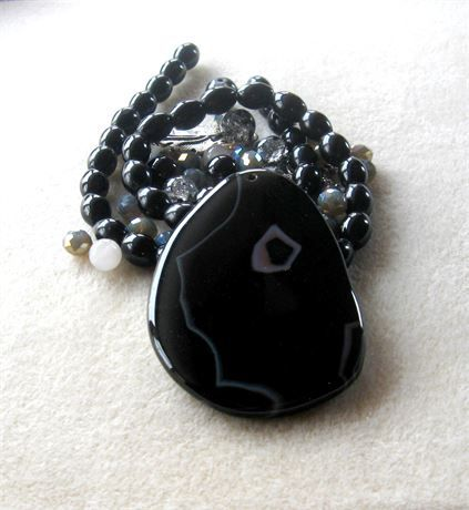 These DIY jewelry kits contain a pendant with coordinating beads and findings so you can easily make a necklace with one stop shopping!    *  black striped agate freeform pendant, top drilled front to back, 47 x 70 x 7mm   *  black agate barrel beads, 15 strand, 6 x 9mm   *  black/silver round crackle beads, 9mm   *  field gray glass faceted rondelle beads, 6 x 8mm   *  antiqued silver spacers, 4mm and 4 x 6mm   *  antiqued silver grape leaf designer toggle clasp, 24mm   Each kit comes w...