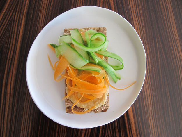 Before work, use a vegetable peeler to make long strands with your carrot and cucumber and pack in a plastic baggie or container. Pack your crispbread and a container of hummus. When ready, spread your hummus on the crispbread and lay down those carrots and cukes.