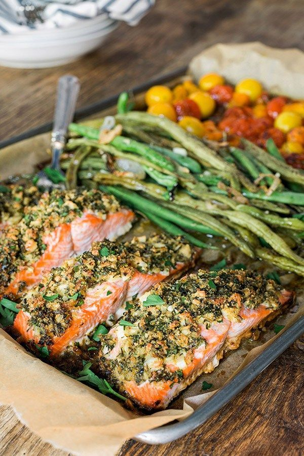 One sheet herb crusted salmon recipe with garlicky green beans & cherry tomatoes.  So healthy, and so easy! Recipe via Waiting On Martha