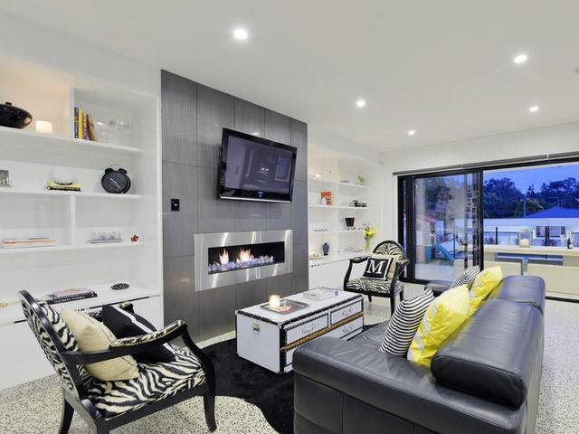 Lounge (open plan off kitchen) - bottom floor. leads right out to backyard/pool. Love the fireplace, and built in cabinetry. Love the polished floorboards