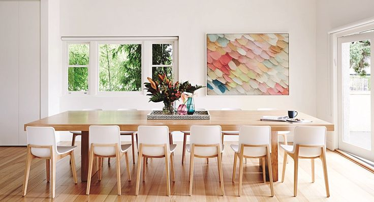 - With its pale, solid timber floor, white and timber chairs and a fabulous 3.6-metre long American oak table, the dining room is a quiet celebration of pared-back Nordic beauty. Picture windows offer a leafy glimpse of the garden, while a focal splash of the prettiest pastel tones comes via a framed Shaynna Blaze canvas.