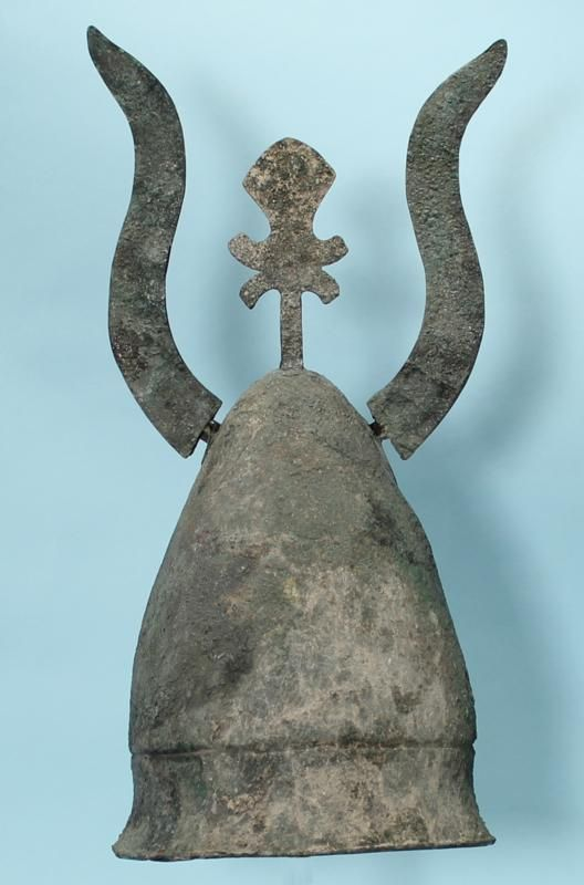 An ancient Greek bronze helmet of the Pilos type, of conical form with a recessed carinated band around the lower portion, with large sheet bronze horns attached to the crown and a crest attachment at the center.