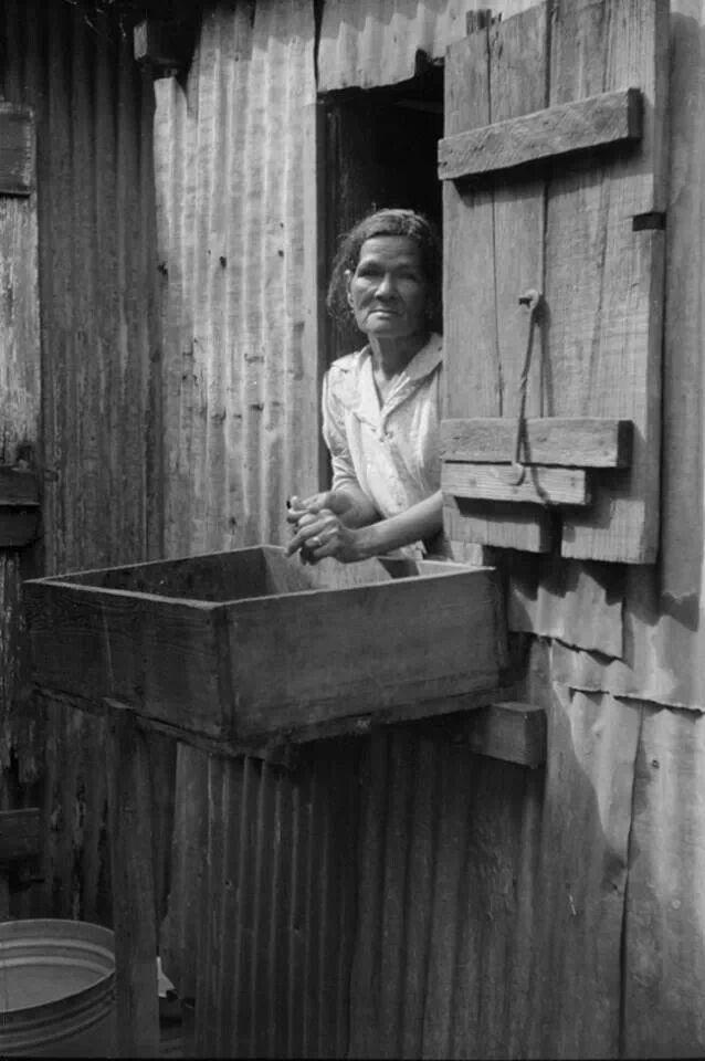 La esposa de un trabajador de la caña asomándose por una ventana de su casita cerca de un cañaveral en Yabucoa, Puerto Rico (1942)