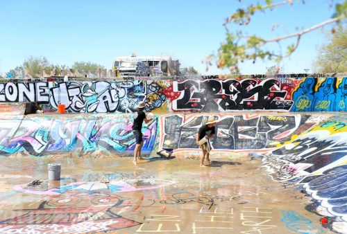 Emptying the water from a rare downpour out of the Slab City skatepark in 100 degree heat