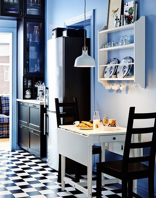 Small IKEA drop-leaf table and two chairs. Plate storage rack on the wall above.